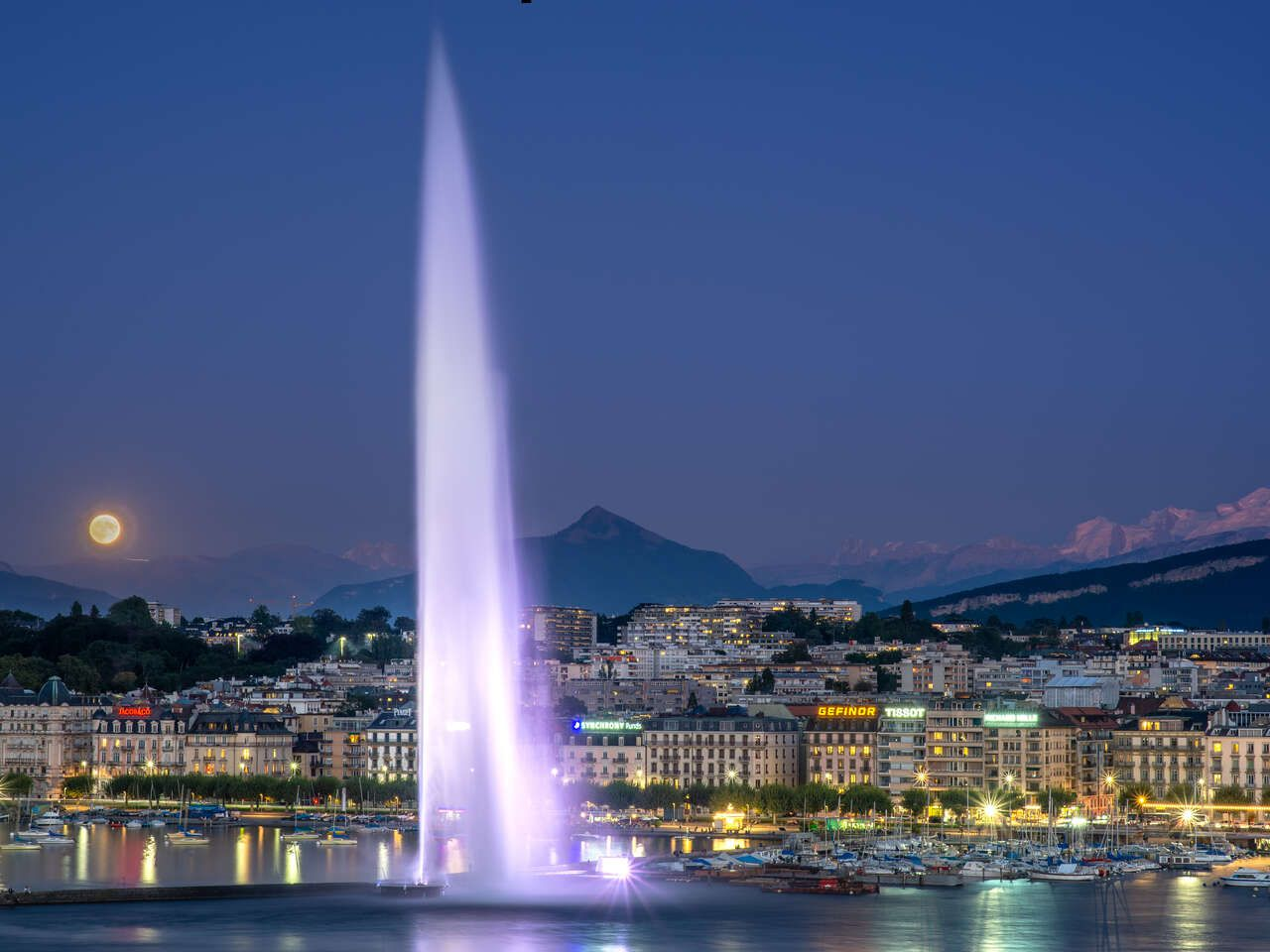The Jet d'Eau illuminated at night with full moon