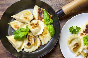pan-fried pierogi dumplings in a frying pan on a table with a plate of pierogis beside