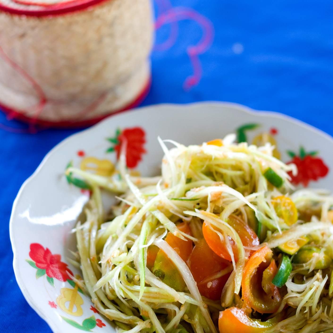 Papaya salad and basket of sticky rice at restaurant.