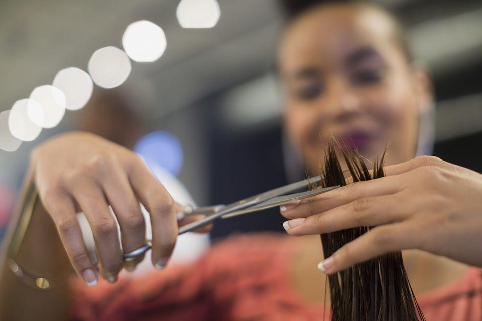 Close up hairstylist cutting hair in hair salon