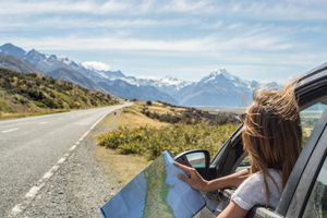 settings Portrait of young woman in car looking at map