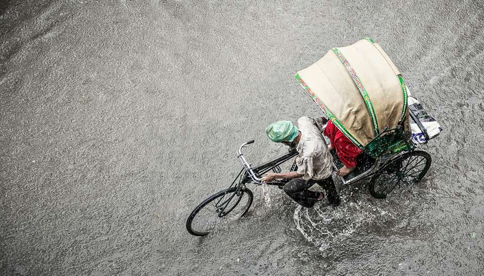 A man pushes a rickshaw during monsoon season in India