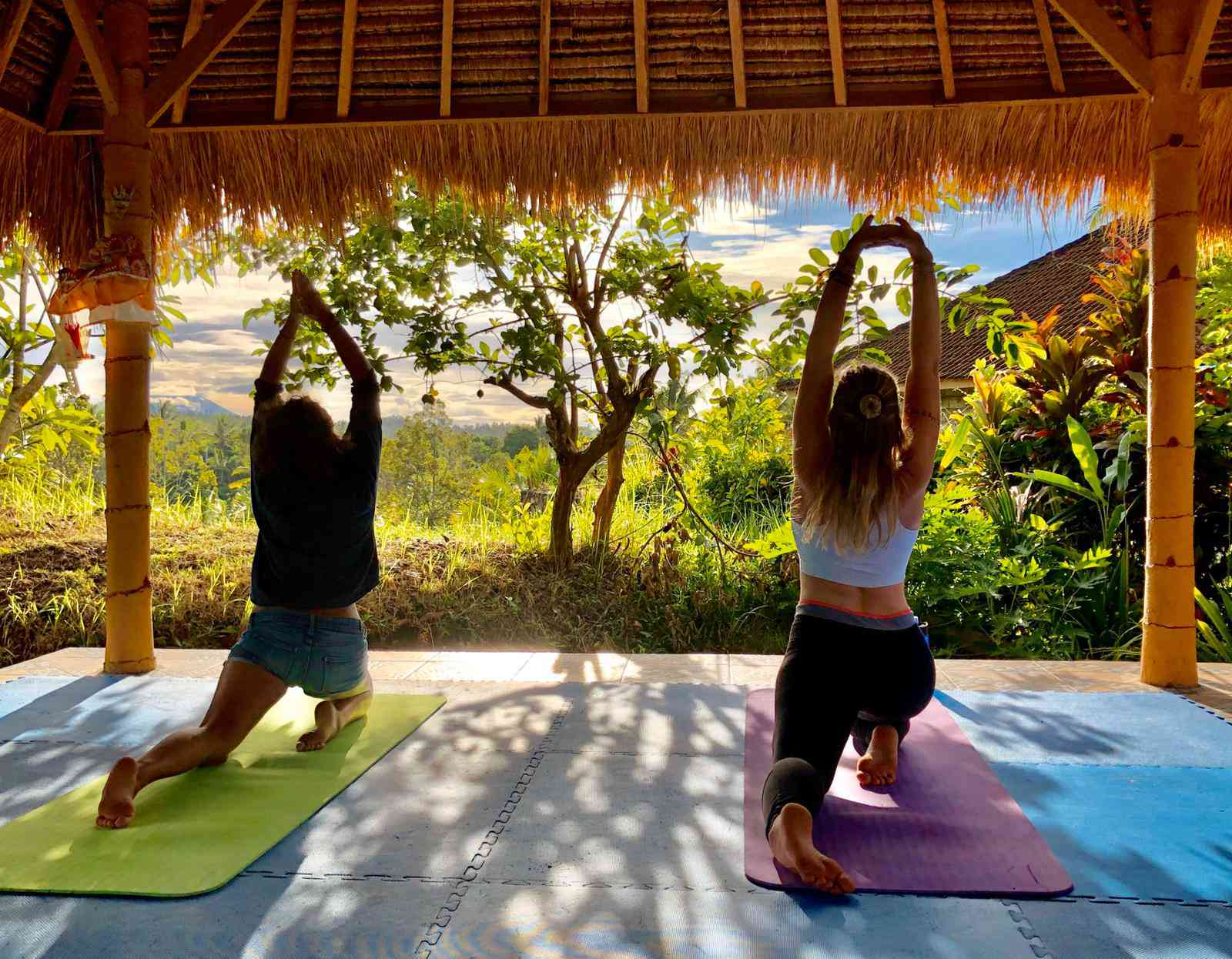 Two people doing yoga with a view of lush Balinese greenery