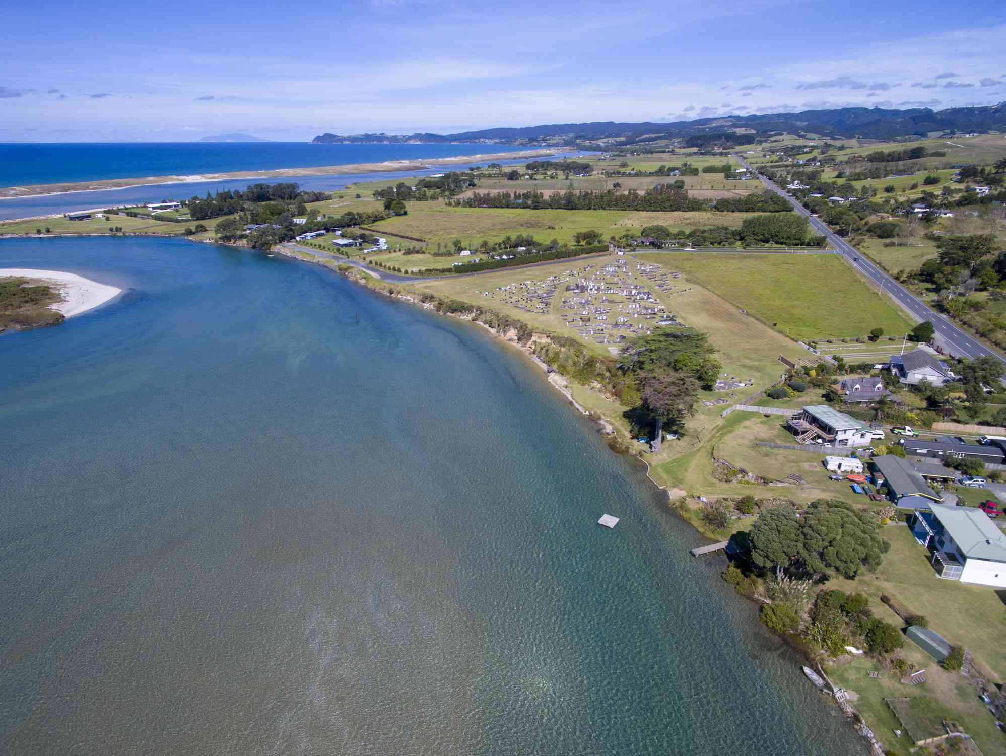 aerial view of Waipu new zealand with a body of water on the left side of the image and the town on the right