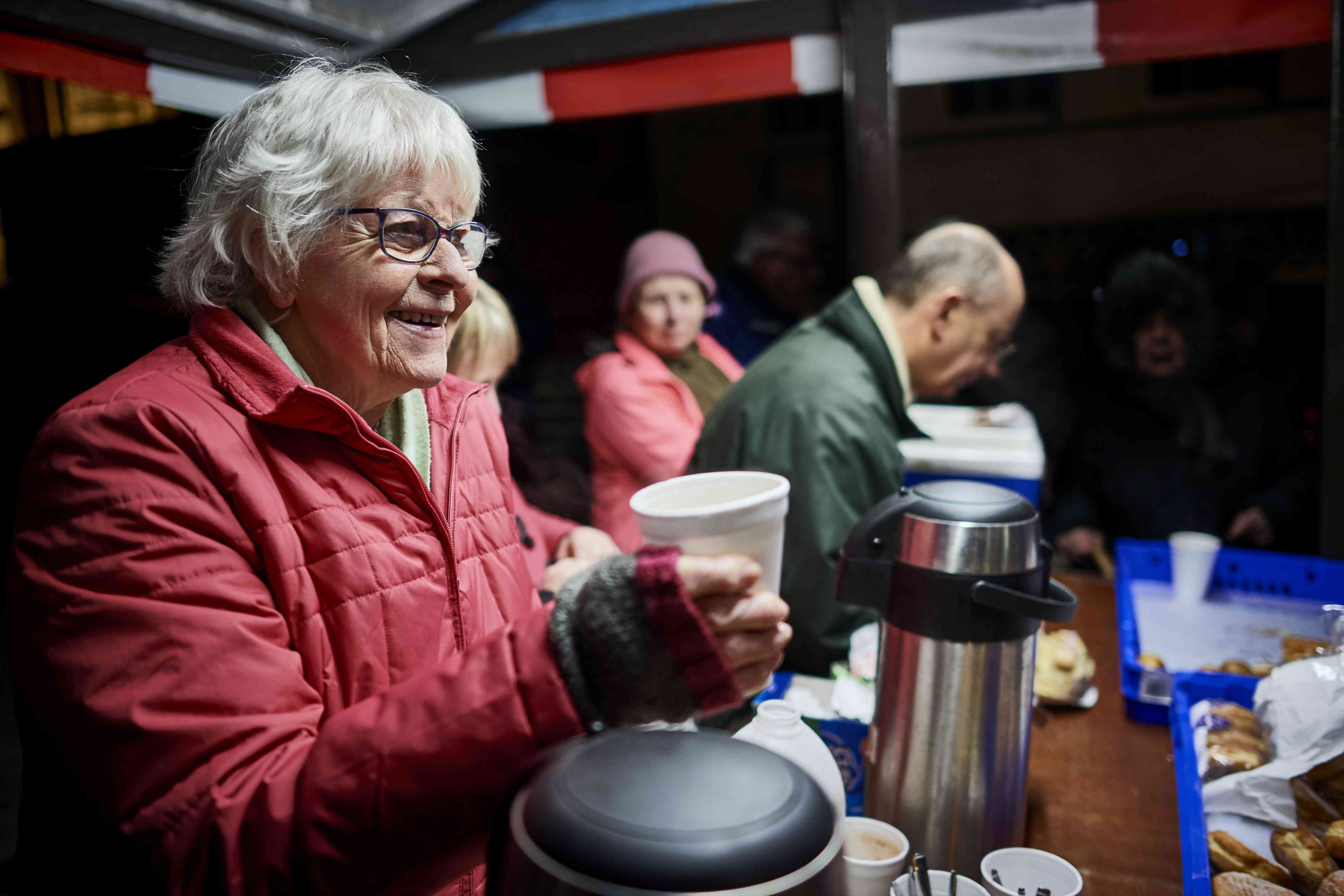 Volunteer serving a hot drink at local soup kitchen