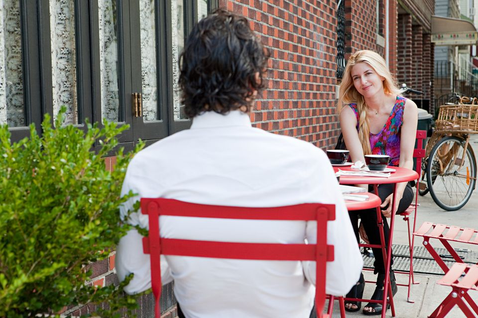 Couple having coffee outside cafe