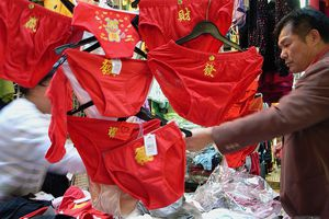 A man shops at a store with red underwear hanging up