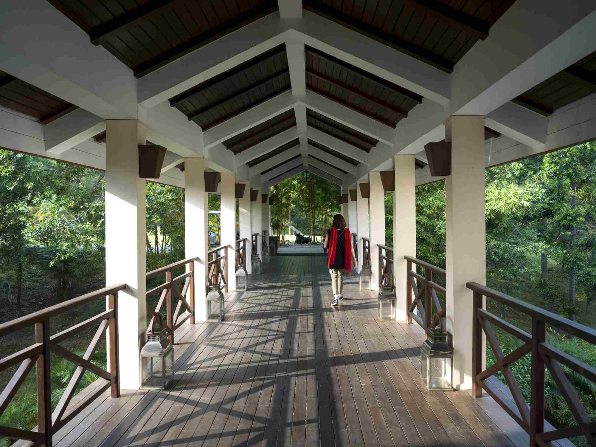 A woman walks down an open-air corridor, Ananda Hotel and Spa