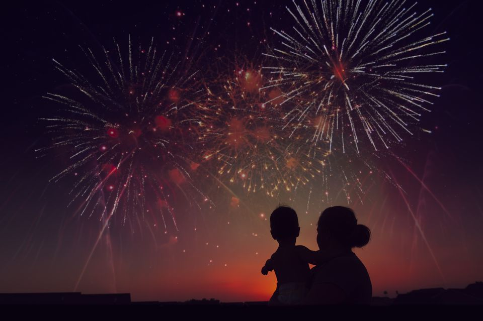 Silhouette of Mother Holding Toddler While Watching Fireworks exploding during Sunset