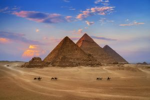 The Egyptian Pyramids of Giza in front of a colorful blue and pink sky