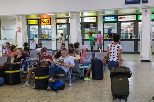 Airline passengers wait for a rental cars at Alghero Airport