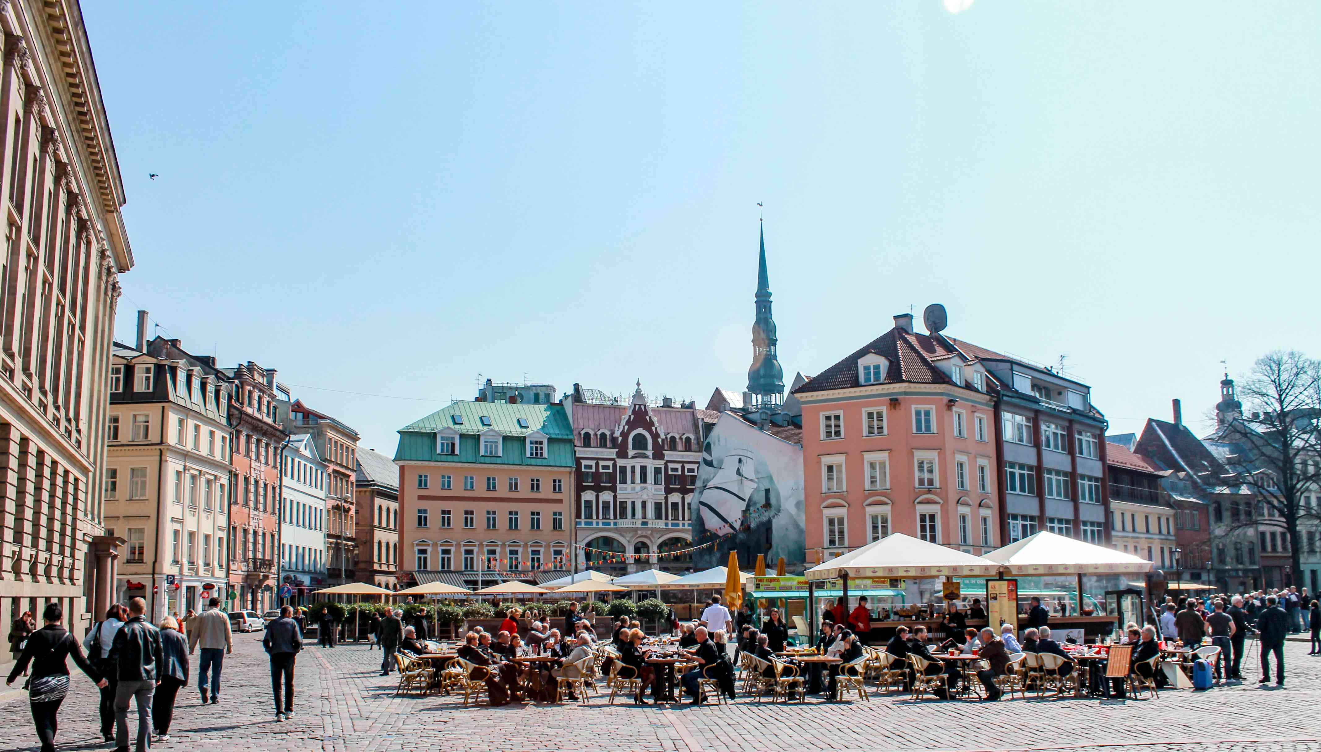 Un grupo de personas sentadas en las mesas afuera en una plaza del pueblo rodeada de coloridos edificios
