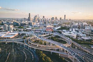 Drone shot of Brisbane with freeway intersection in foreground and city skyline in background