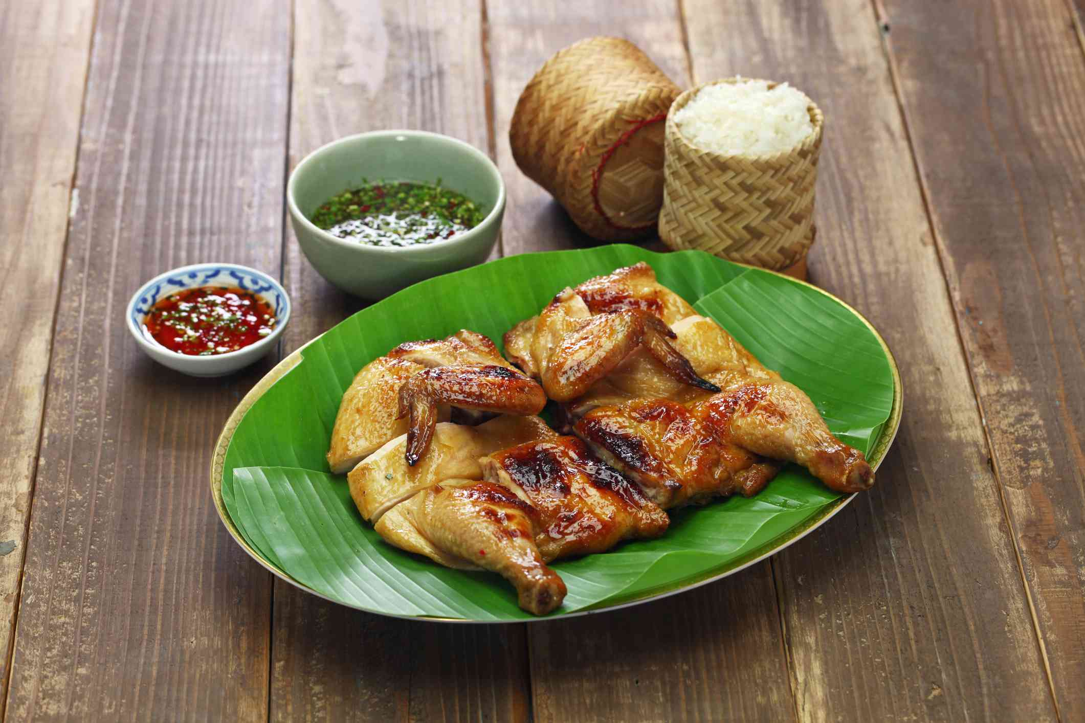 cooked and cut whole chicken on a plate with banana leaves. there is also a wicker container with rice and two sauce bowls on the table next to the chicken