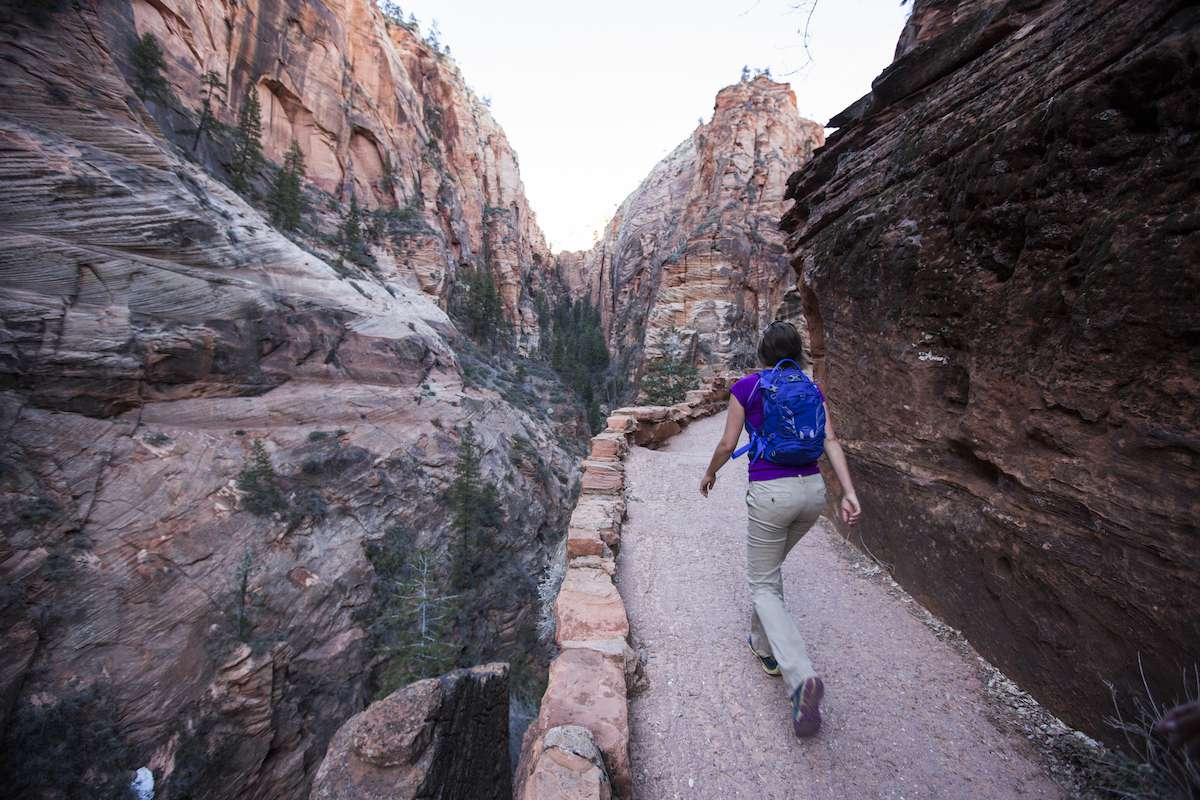 A woman with a blue backpack hikes a trail into Zion Canyon