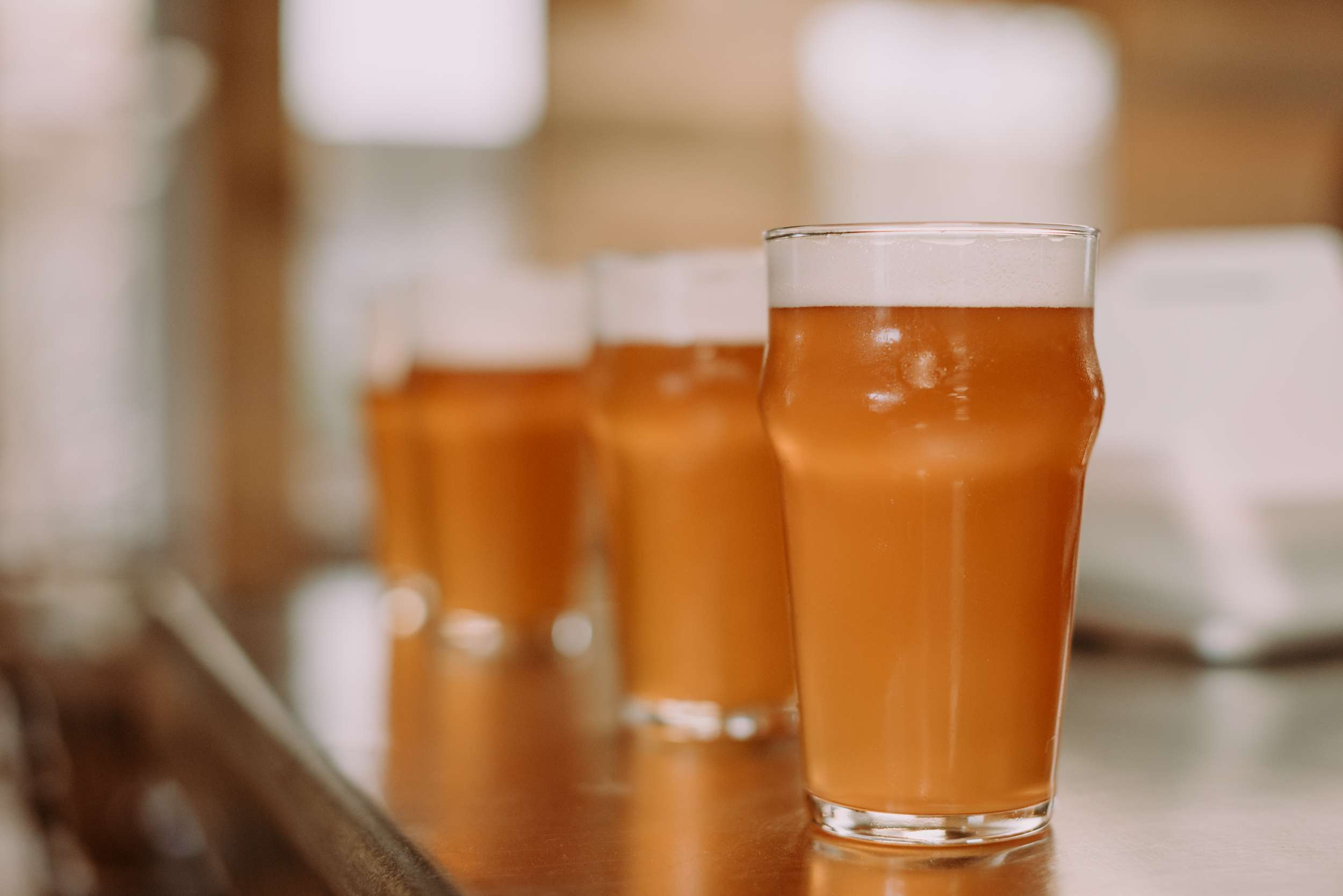 four pint glasses on a bar filled with amber-colored beer. Only one glass of beer is in focus