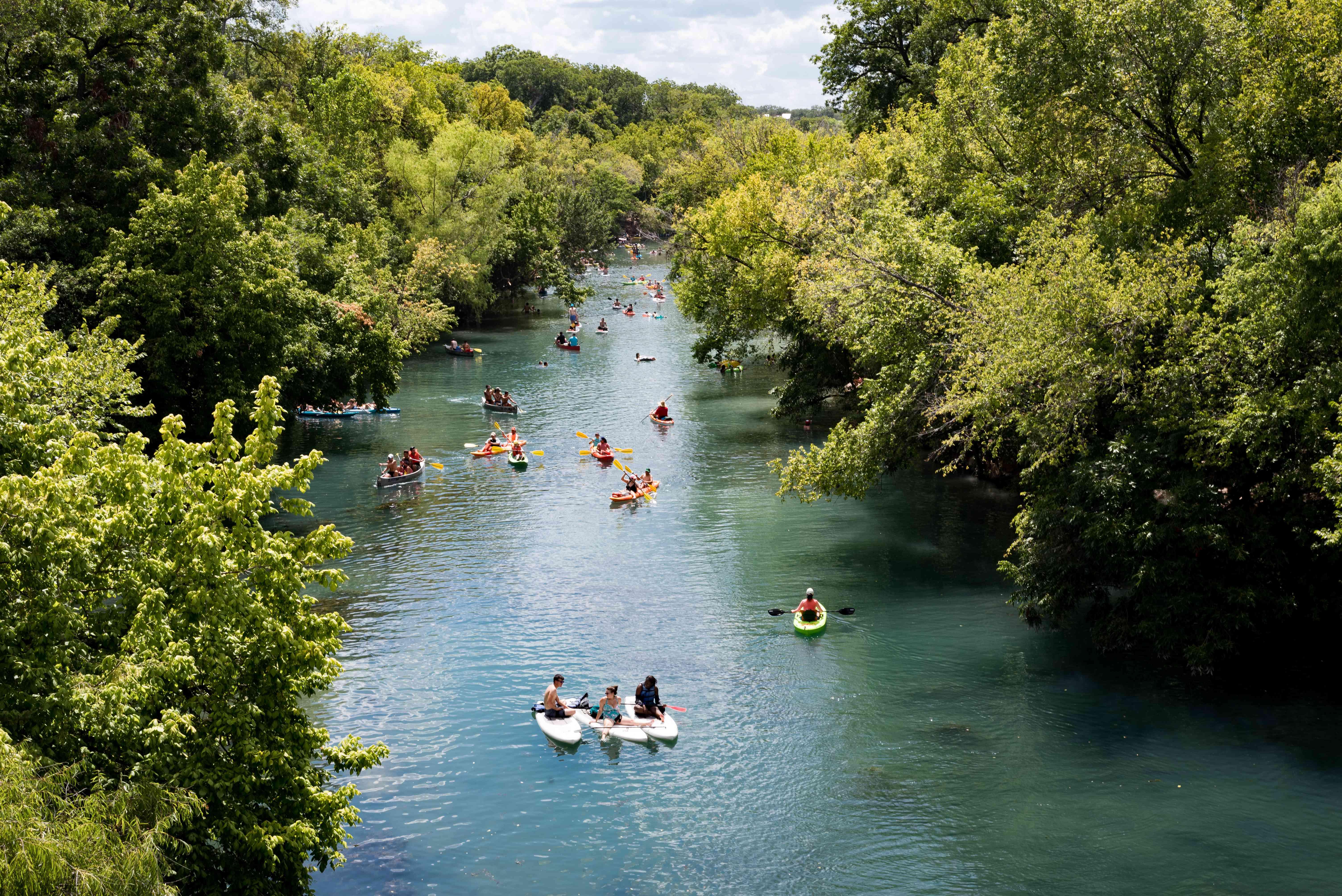 Gente remando y haciendo kayak por el lago Lady Bird rodeado de frondosos árboles verdes