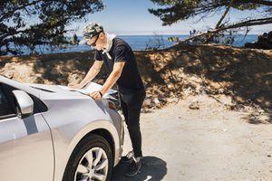 Man on road trip reading map on car hood, Big Sur, California, USA
