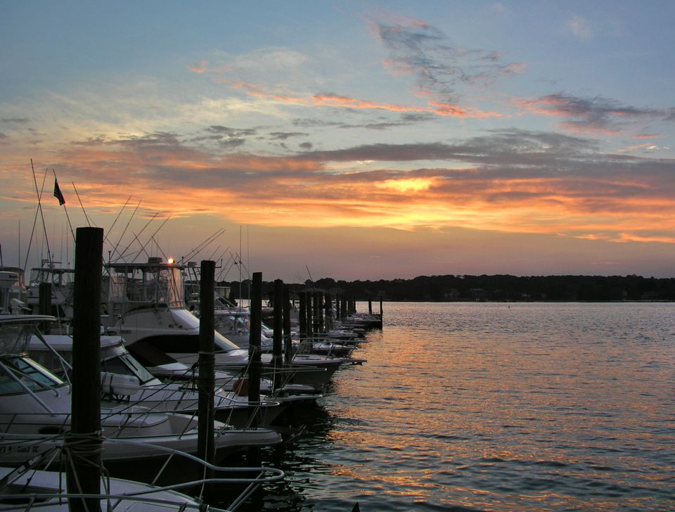 Boats lined up in a harbor at sunset