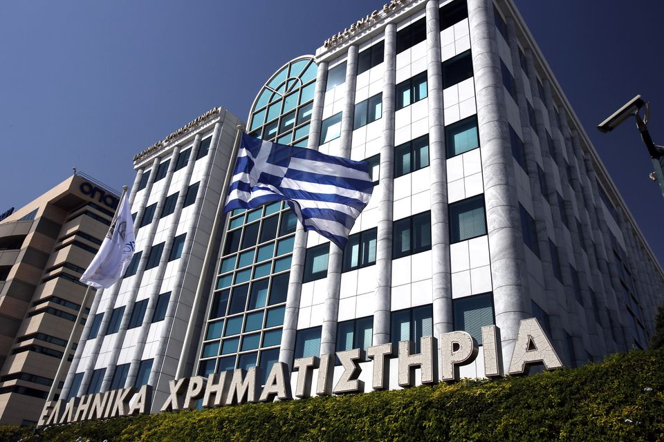 The Greek flag flies outside the Greek Stock Exchange