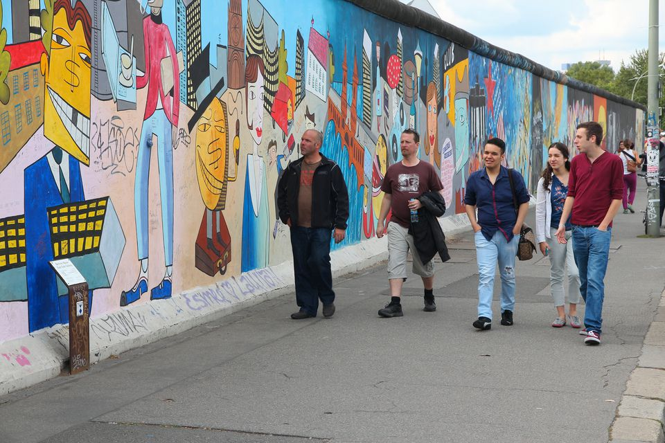 Tourists visit free public urban art of East Side Gallery at public street in Berlin.