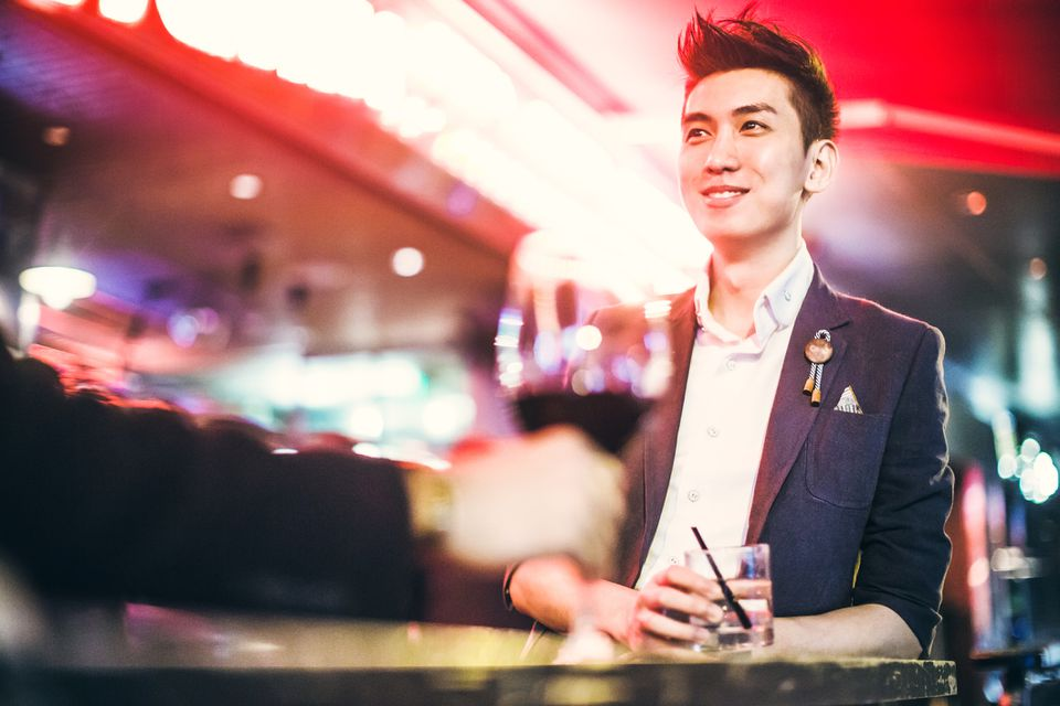 A young adult man enjoys a drink at a bar or club in downtown Hong Kong
