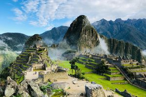 Ancient Inca ruins rise from the mist with the Andes Mountain in the background