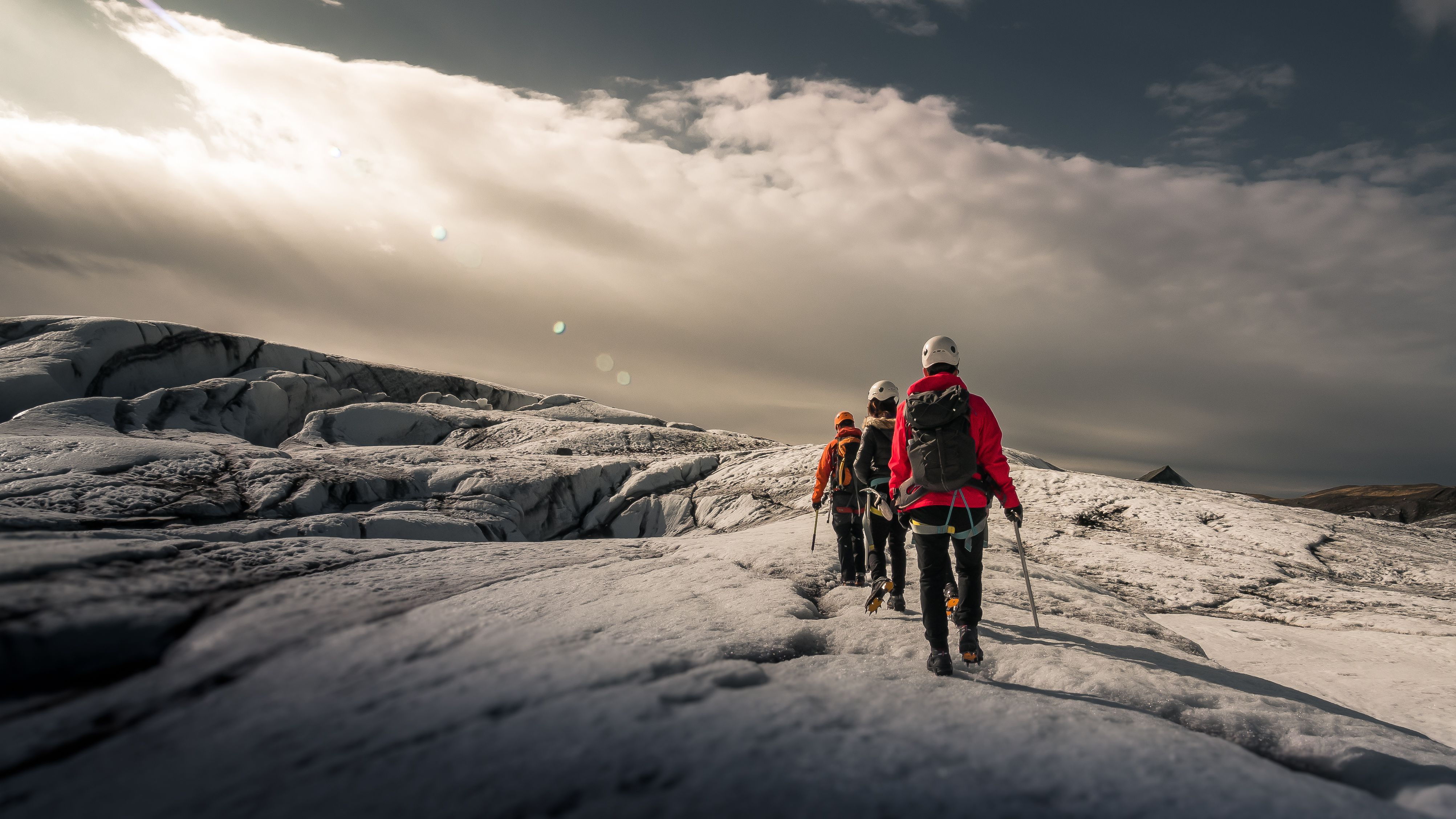 a group of people in full gear hiking on a glacier