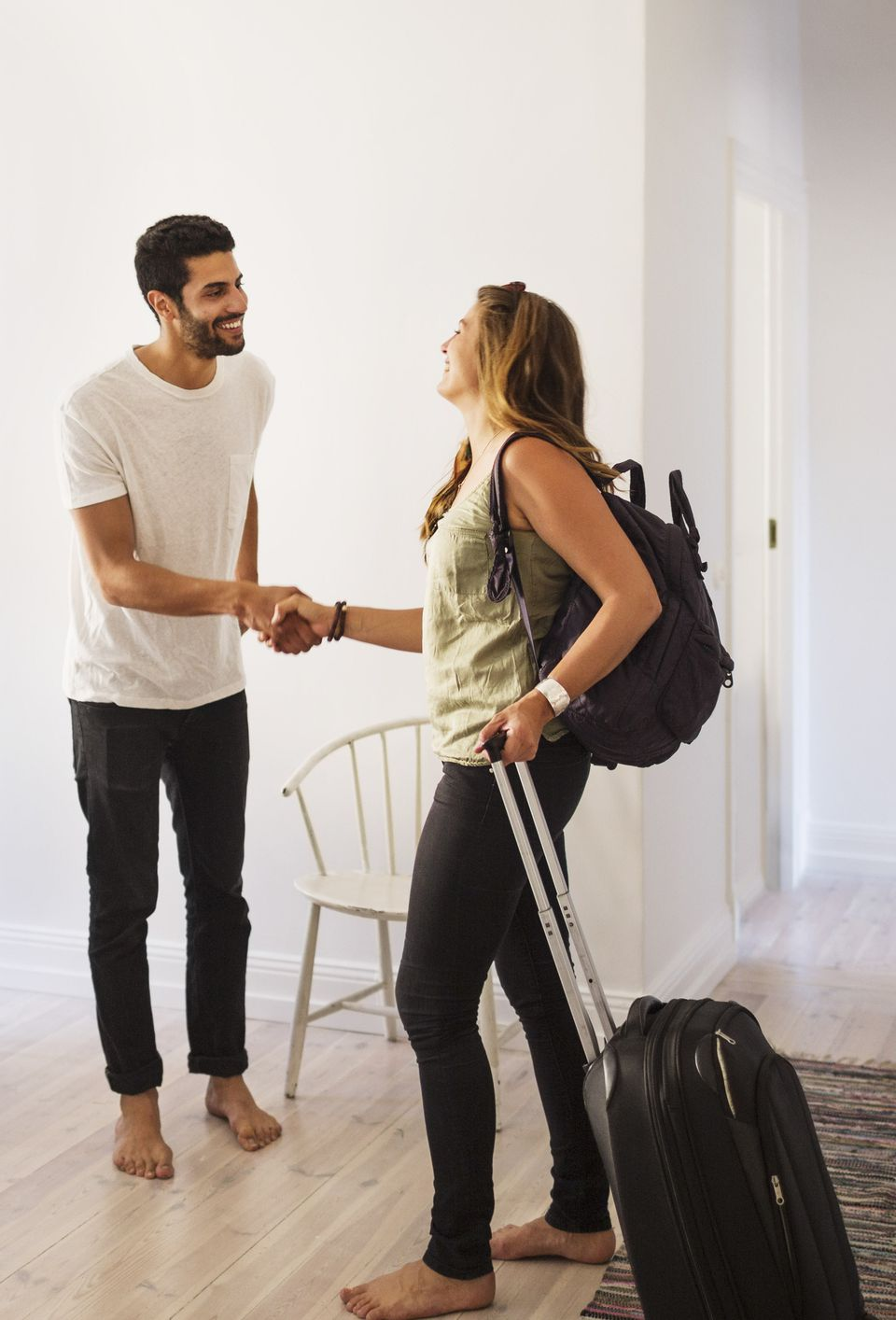 Couchsurfing host greets a guest with luggage