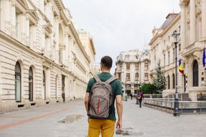 Young man with backpack walking on the street