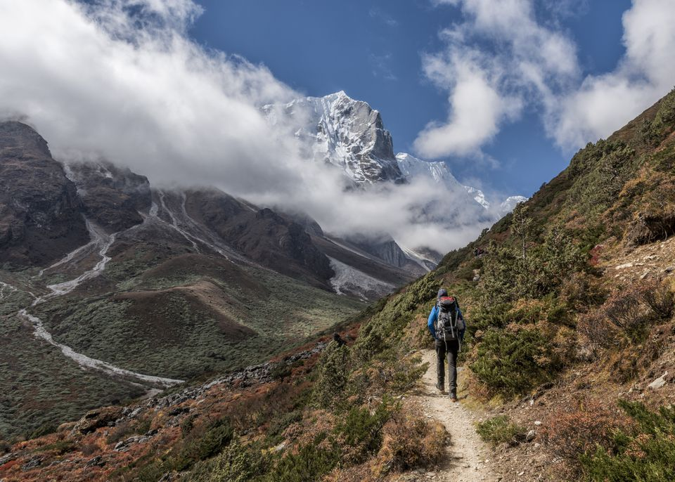 person with backpack walking along a footpath in the mountains, with clouds and mountains behind