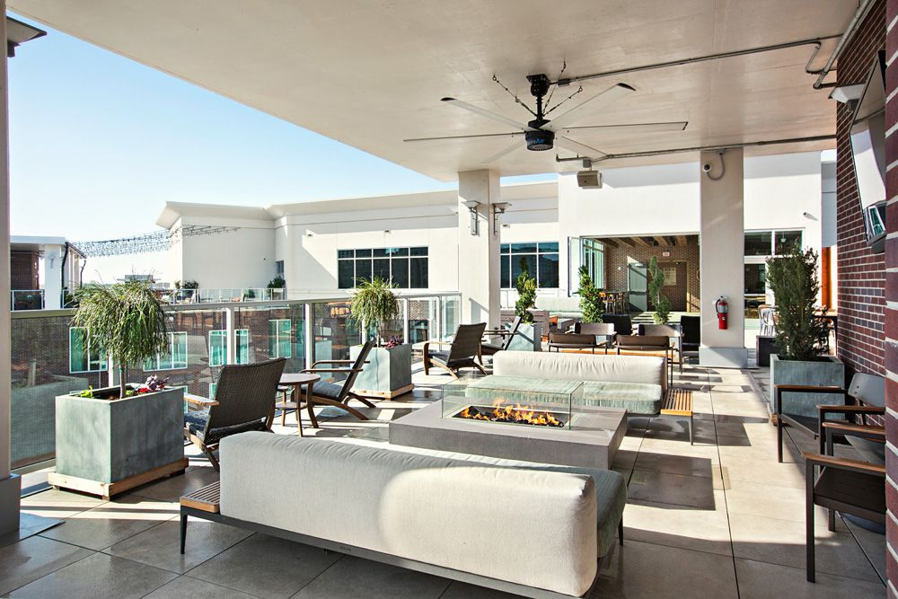 couches and a fireplace on an outdoor patio lounge