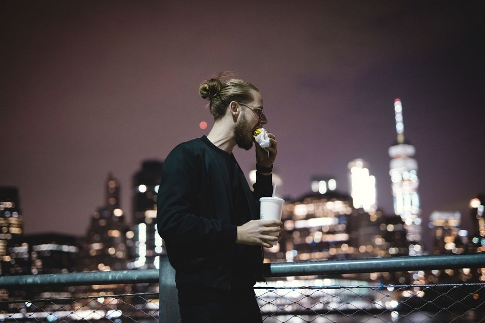 Man eating in Brooklyn in front of NYC skyline