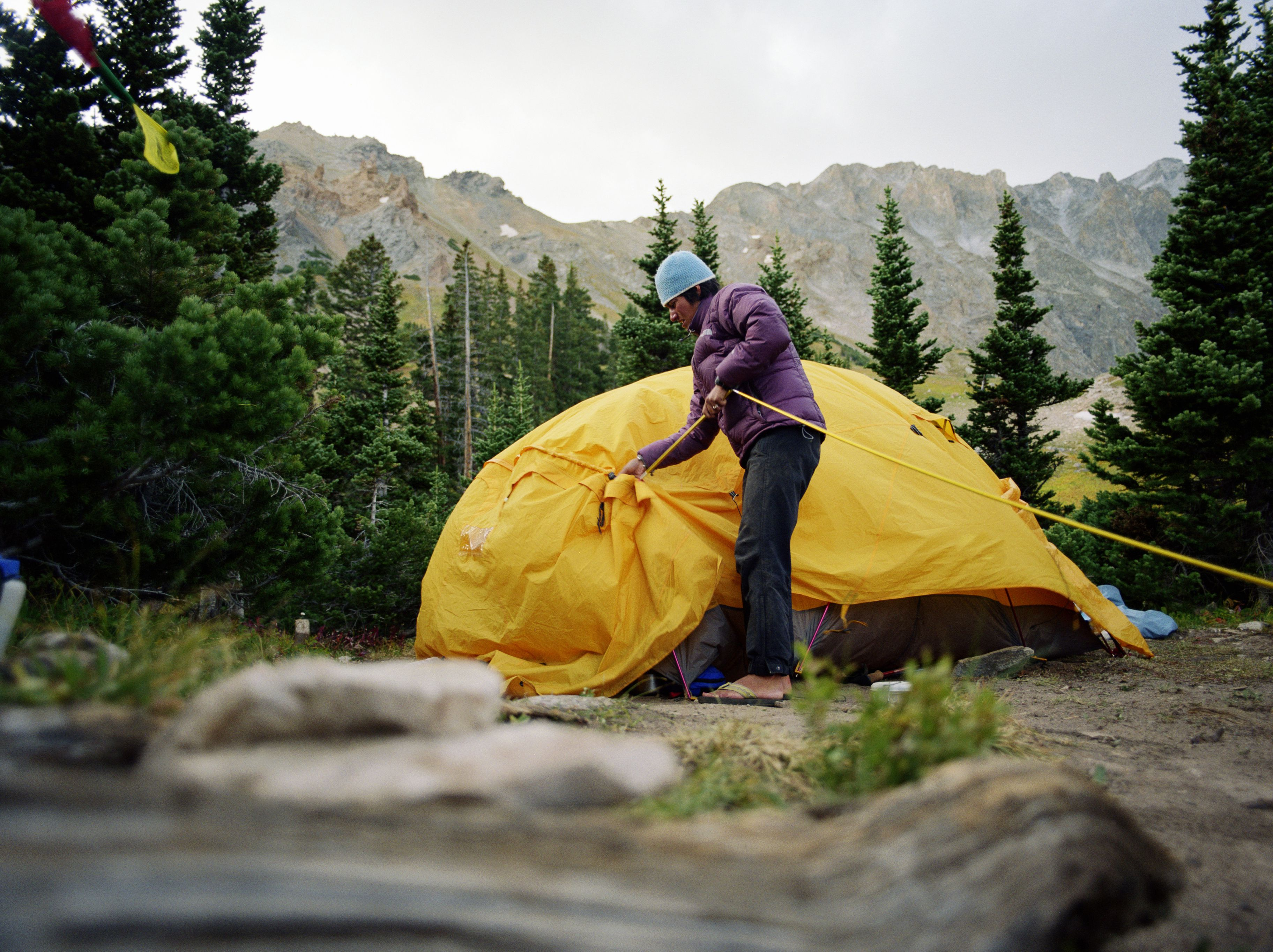 Woman setting up camp, erecting tent