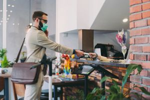 Man in a surgical mask checking in at a hotel desk