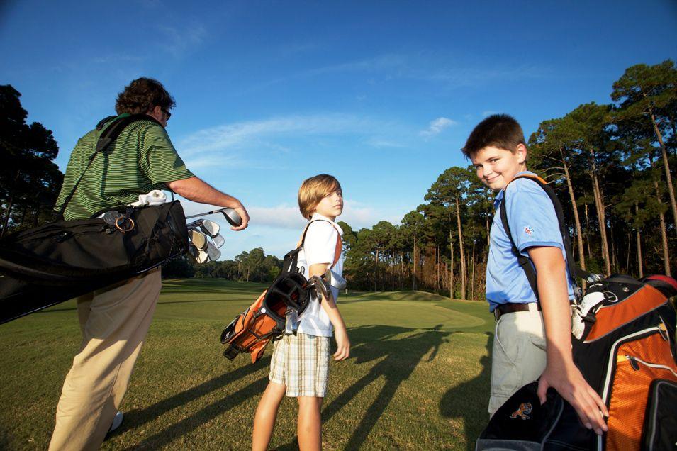 man and two boys with golf bags at Jekyll Island Club: Jekyll Island, GA