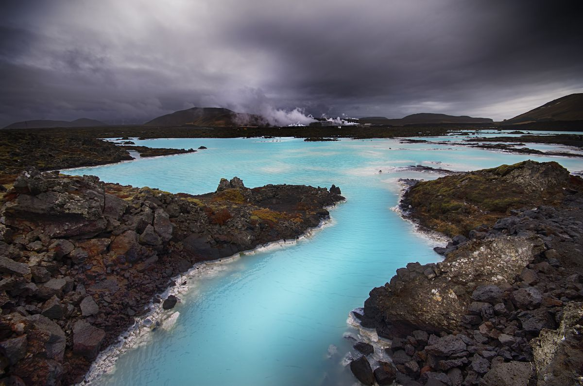 The blue waters of a hot spring stretching into the distance along a rocky shore.