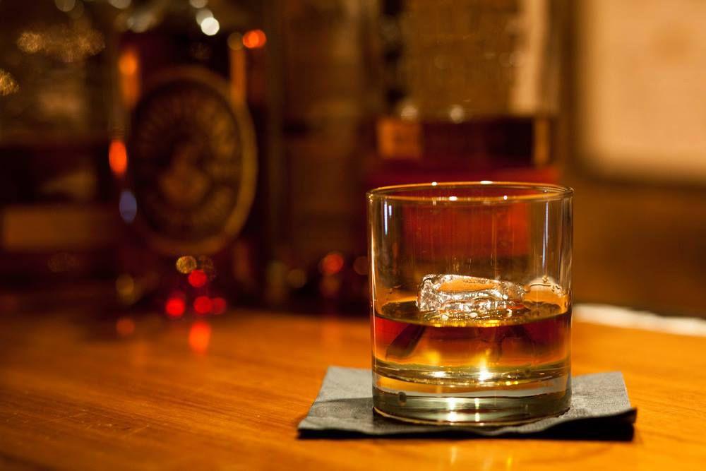 Un vaso de bourbon con hielo en un bar