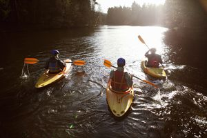 three kayakers rowing together on a still lake