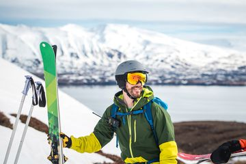 Man with skis standing outside