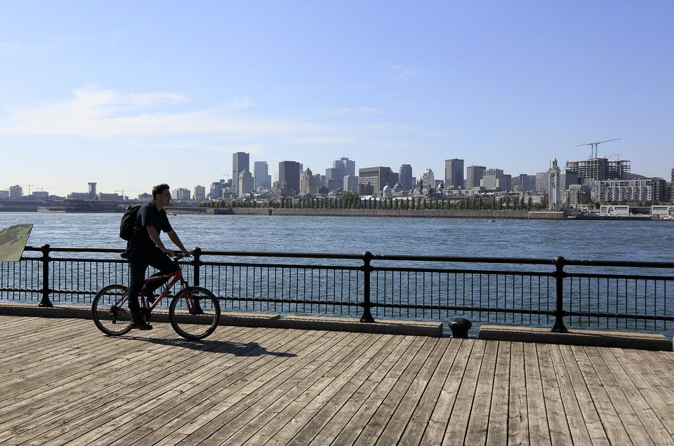 A bicyclist rides along Montreal's Old Port, with the city skyline in the background