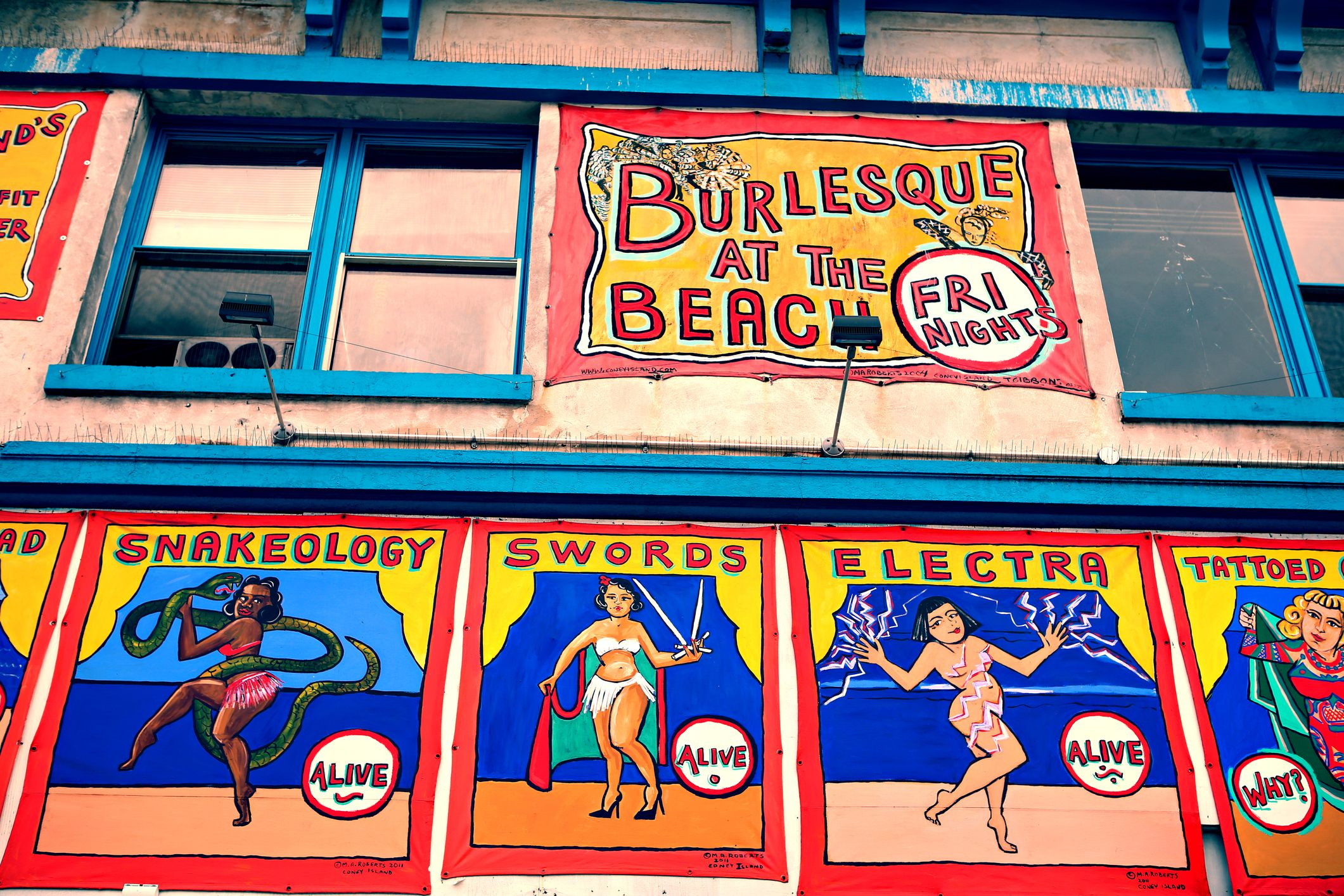 Colorful iconic vintage freak show banners and murals hanging on the facade of the Coney Island Museum building in Coney Island, Brooklyn