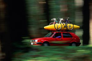 RED CAR WITH KAYAK DRIVING IN FOREST