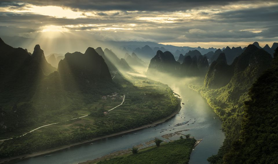 Sun breaking through cloudy sky mountain landscape in China