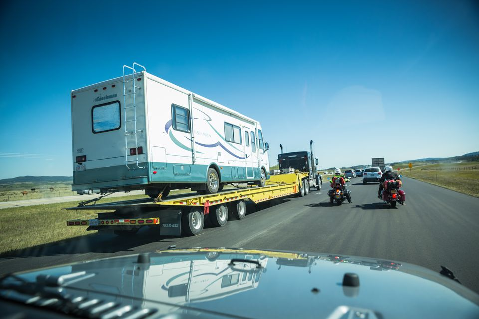 broken RV vehicle being transported on freeway