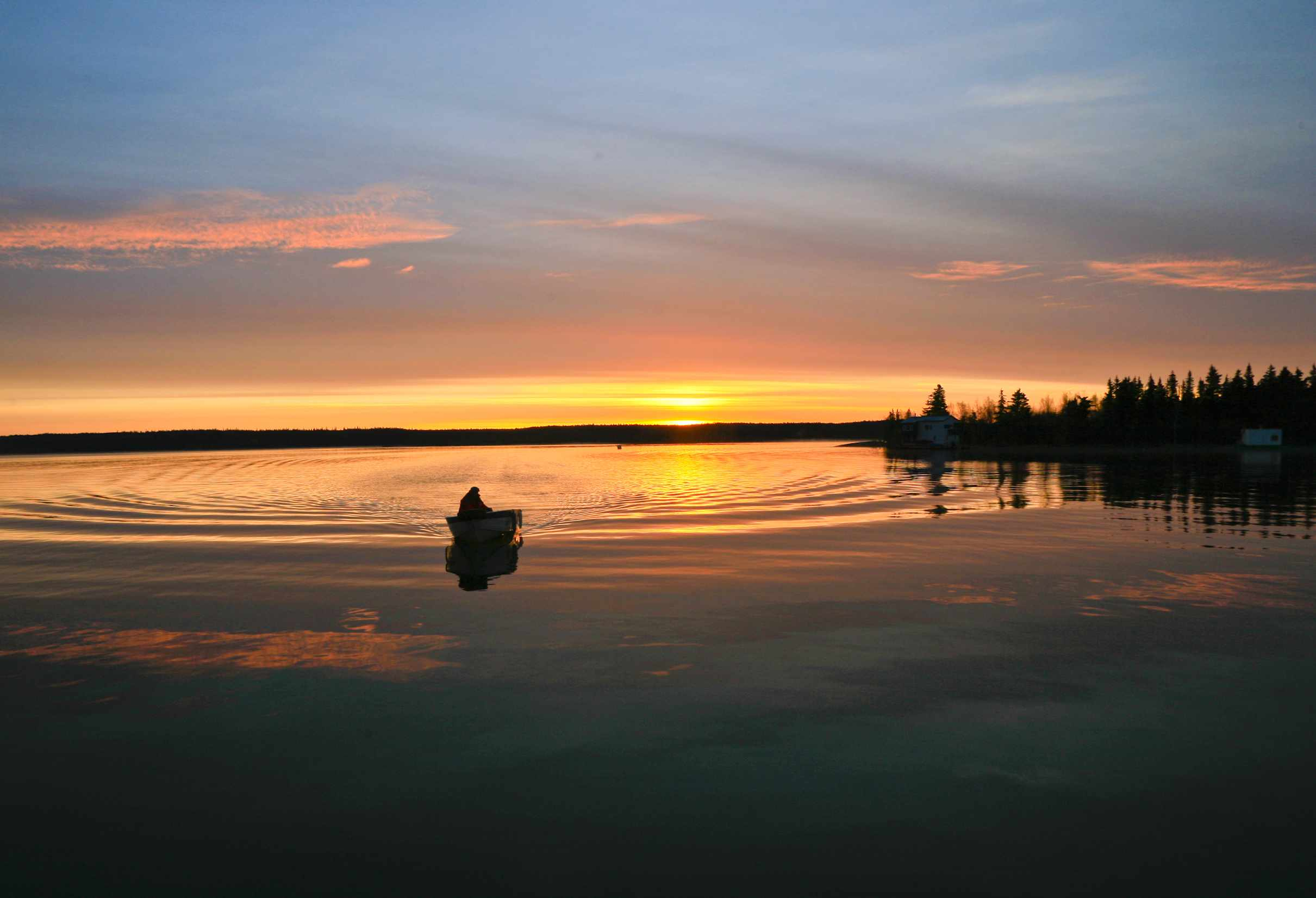 Outboard Boat on a lake Silhouetted by Sunrise