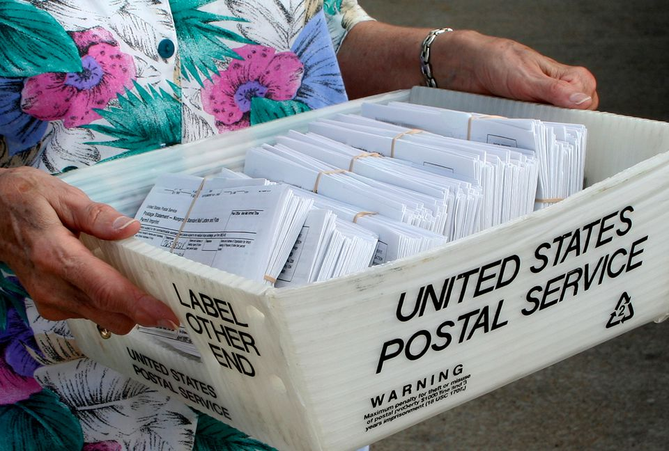 Woman's hands carrying USPS box with letters