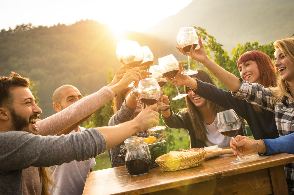 A group of people toasting with wine glasses with at golden hour
