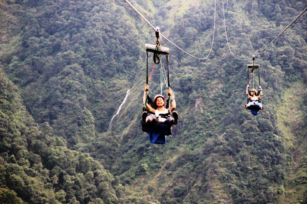 two ziplines speeding down wire tracks amid forested hills and a small waterfall