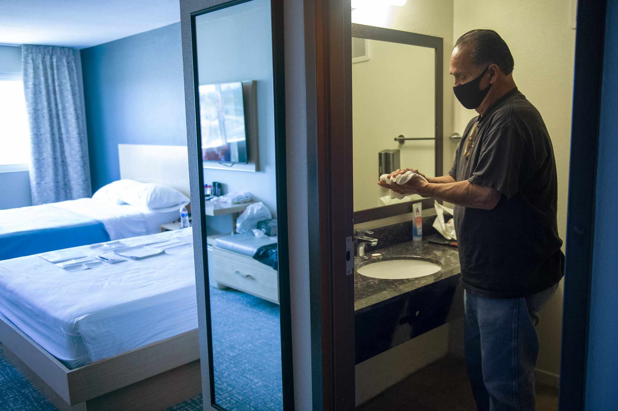 A man washing his hand in a hotel room provided by Project Roomkey